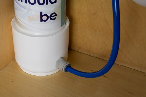 Glacier Compact inline undersink water filter installed with plastic fittings closeup.